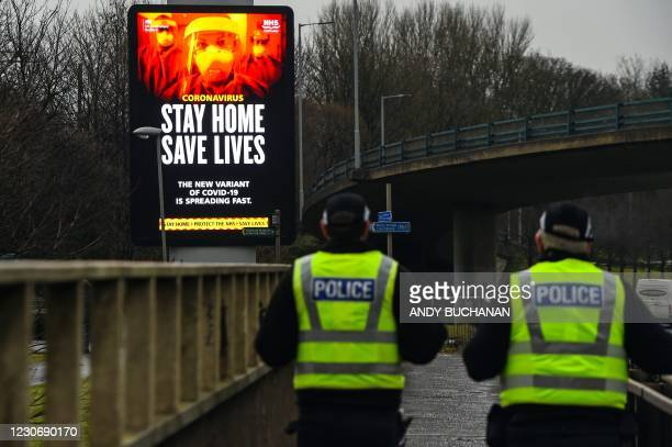 Police officers walk past a Covid-19 information board alongside the Clydeside Expressway in Glasgow on January 20, 2021.