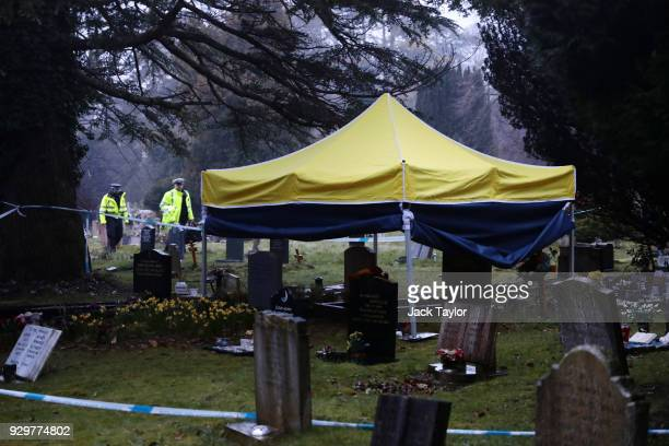 Police officers walk past a forensics tent over the grave of former Russian double agent Sergei Skripal's wife Lyudmila in London Road cemetery on...