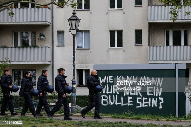 Police officers walk past a graffiti painted on a wall and reading How can anyone be a cop in Berlin's Kreuzberg district on May 1 during a May Day...