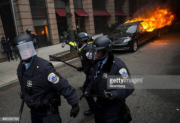 Police officers walk past a limousine set on fire by protesters during a demonstration at the 58th presidential inauguration in Washington DC US on...