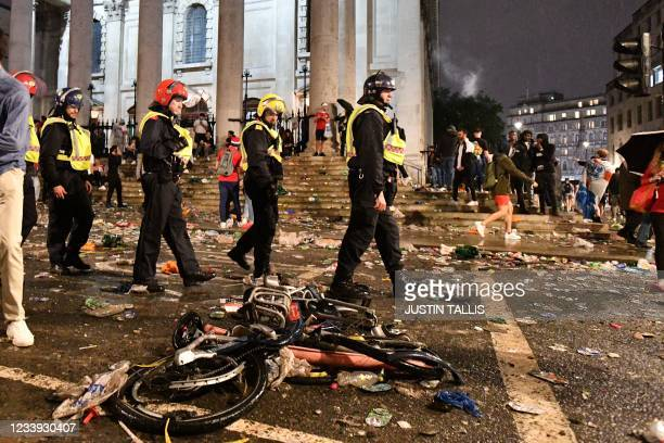 Police officers walk past broken bicycles and rubbish outside St. Martin-in-the-Fields church on the edge of Trafalgar Square after a live screening...