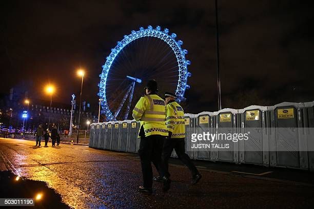 Police officers walk past portaloos set up in the secure ticketed area in the shadow of the London Eye ahead of the New Year's Eve fireworks in...
