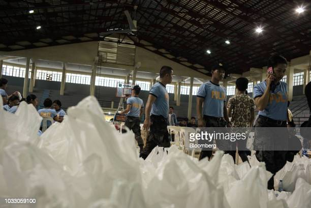 Police officers walk past relief supplies at a makeshift disaster relief operations center ahead of Typhoon Mangkhut's arrival in Tuguegarao Cagayan...