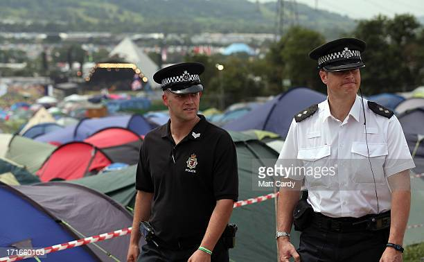 Police officers walk past tents at the Glastonbury Festival of Contemporary Performing Arts site at Worthy Farm Pilton on June 27 2013 near...