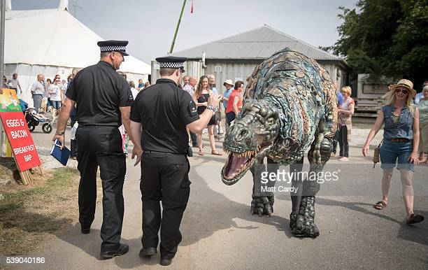 Police officers walk past the Eden Project's life-size juvenile Tyrannosaurus rex that has been brought as a preview to the nearby attraction's...