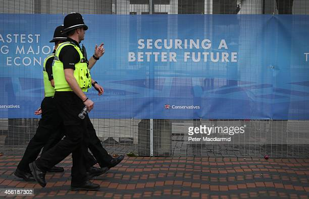 Police officers walk the perimiter fence at the International Convention Centre ahead of the Conservative party conference on September 27 2014 in...