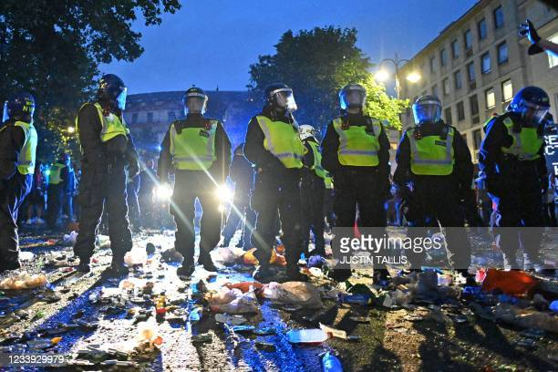 Police officers walk through the rubbish on the edge of Trafalgar Square after a live screening of the UEFA EURO 2020 final football match between...