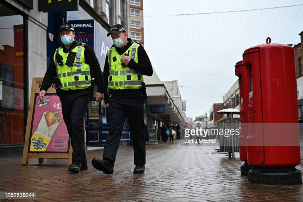 Police officers walk through the town centre on October 29, 2020 in Motherwell, Scotland. The levels of coronavirus restrictions to be placed on each...