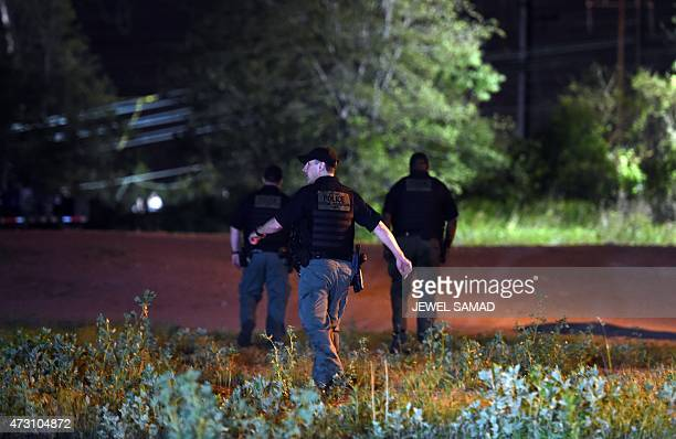 Police officers walk to the site of an Amtrak train crash in Philadelphia Pennsylvania on May 13 2015 At least five people were killed and dozens...