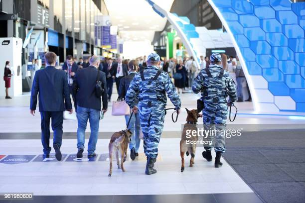 Police officers walk with security dogs through the main hall of the ExpoForum at the St Petersburg International Economic Forum in Saint Petersburg...