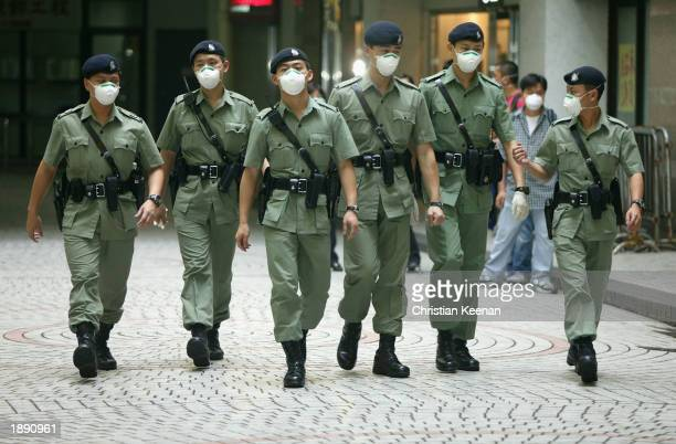 Police officers walking in Amoy Gardens April 2 2003 in Hong Kong wear masks to prevent infection from SARS virus The Hong Kong government have sent...