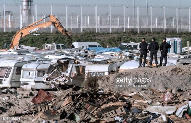 TOPSHOT Police officers watch an excavator clearing caravans in the 'Jungle' migrant camp on October 31 2016 in Calais northern France French...