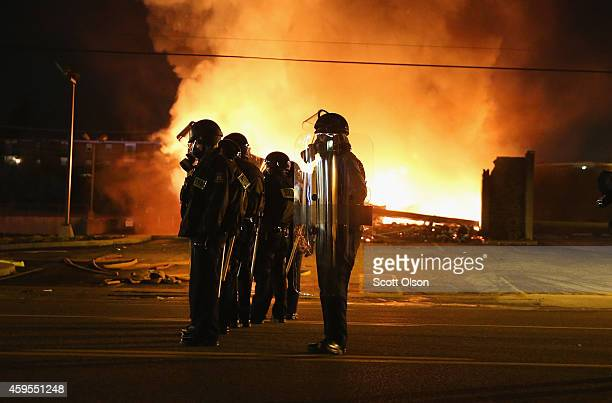 Police officers watch as a business burns after it was set on fire during rioting following the grand jury announcement in the Michael Brown case on...
