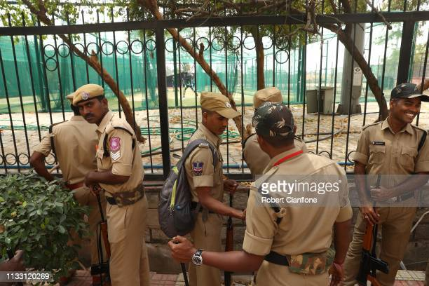 Police officers watch as Australian players warm up in the nets prior to game one of the One Day International series between India and Australia at...