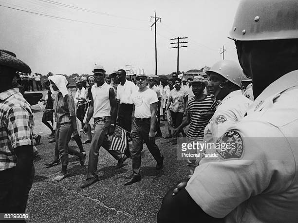 Police officers watch as civil rights campaigners take part in the Meredith Mississippi March near Jackson Mississippi June 1966 The march began when...
