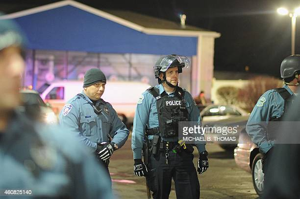 Police officers watch as demonstrators a protest outside the Mobil OnTheRun gas and convenience store in Berkeley Missouri on December 24 2014 In the...