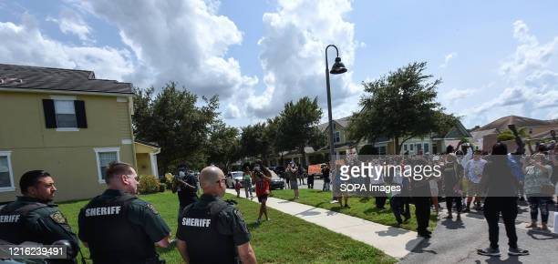 Police officers watch as demonstrators march outside a home owned by Derek Chauvin, the Minneapolis police officer filmed kneeling on the neck of...