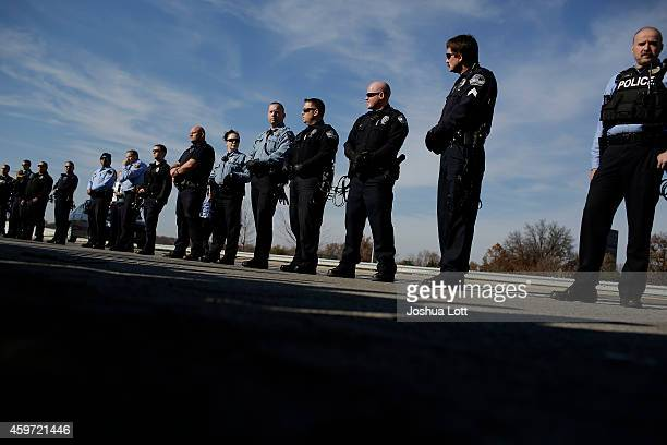 Police officers watch as demonstrators protest the shooting death of Michael Brown November 29 2014 in Brentwood Missouri Brown a 18yearold black...