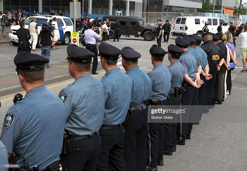 MIT Police officers watch as the motorcade containing alleged Boston Marathon bomber Dzhokhar Tsarnaev leave the John Joseph Moakley United States Courthouse following his appearance.