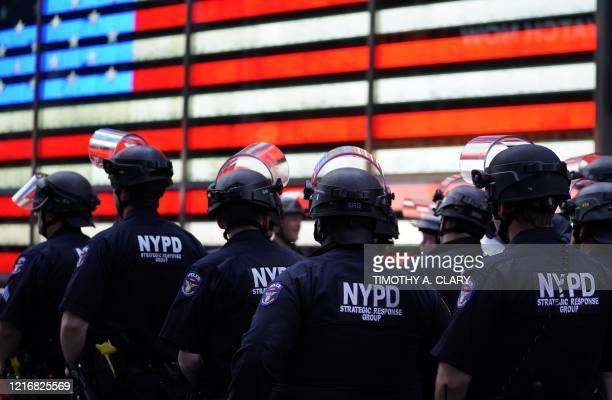 "Police officers watch demonstrators in Times Square on June 1 during a ""Black Lives Matter"" protest. - New York's mayor Bill de Blasio today declared..."