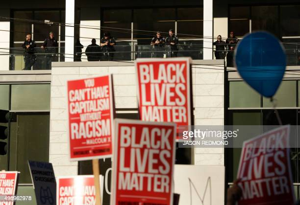 Police officers watch from a shopping mall balcony as a Black Lives Matter protest occurs below on Black Friday in Seattle Washington on November 27...