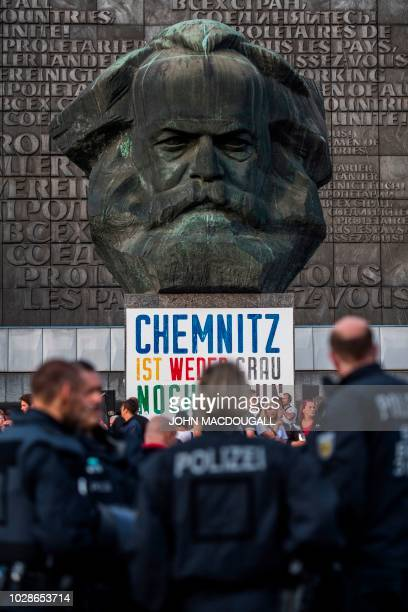 Police officers watch over a march organised by the rightwing populist Pro Chemnitz movement in front of the city's Karl Marx monument on September 7...