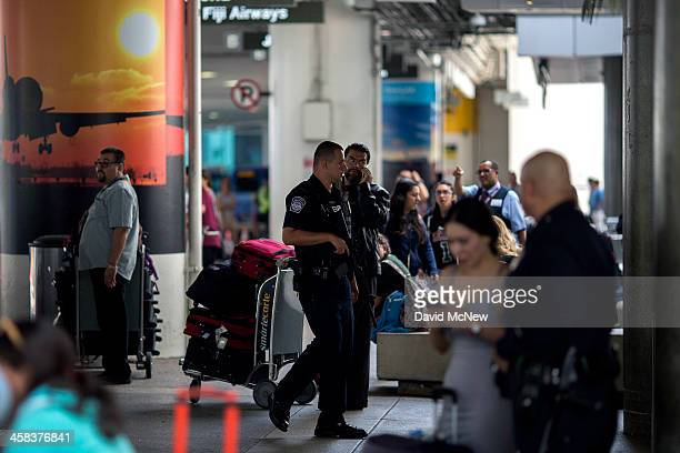 Police officers watch over travelers at Los Angeles International Airport on July 2 2016 in Los Angeles California Security is stepped up for the...