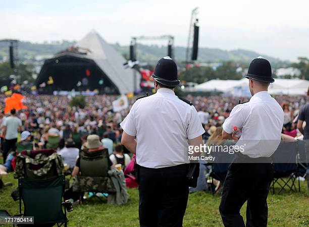 Police officers watch the main Pyramid Stage at the Glastonbury Festival of Contemporary Performing Arts site at Worthy Farm Pilton on June 28 2013...