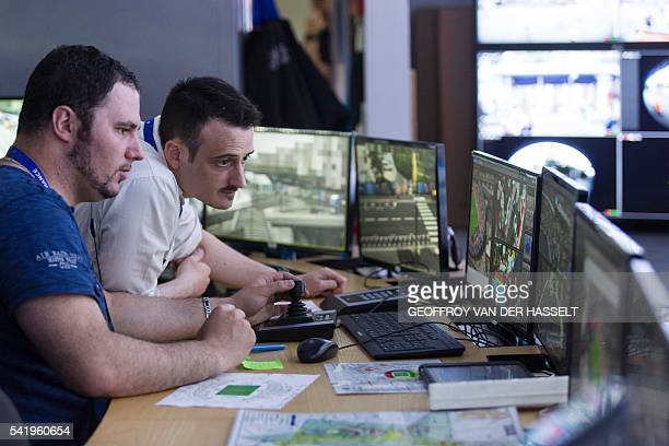 Police officers watch the surveillance screens at the control center at the Parc des Princes on June 21 2016 in Paris during the Euro 2016 group C...