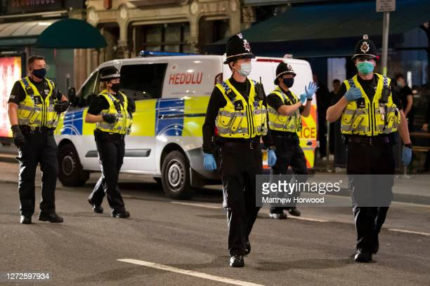 Police officers wear face masks as they attend to a brawl on St. Mary Street on September 12, 2020 in Cardiff, Wales. Lockdown rules have been...