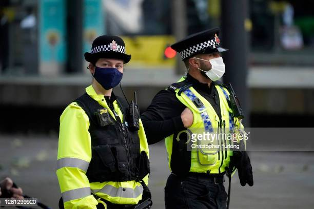 Police officers wear face masks as they patrol the city centre on October 20, 2020 in Manchester, England. Talks between the Housing and Communities...
