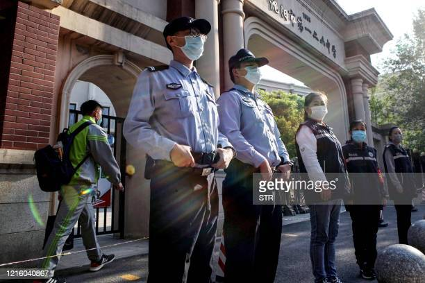 Police officers wear face masks as they stand guard at the entrance of a middle school in Shenyang, China's northeastern Liaoning province on May 29,...