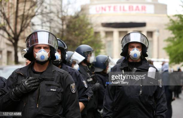 Police officers wear face masks while monitoring a demonstration against restrictions on public life designed to stem the spread of the coronavirus,...