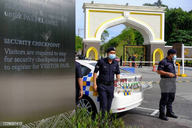 Police officers wear protective masks while staning outside the main entrance of the Istana Negara palace in Kuala Lumpur Malaysia on Tuesday Oct 13...