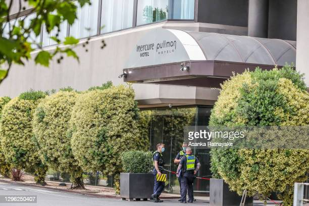 Police officers wearing a mask is seen at the entrance of The Pullman Hotel in Albert Park which is one of the three hotels being used for quarantine...