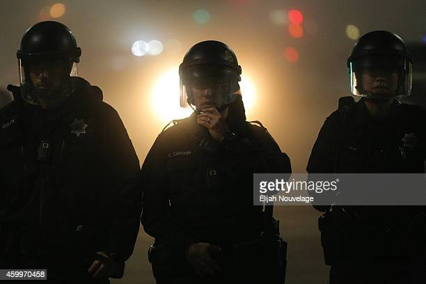 Police officers wearing body cameras form a line in East Oakland on the second night of demonstrations following a Staten Island New York grand...