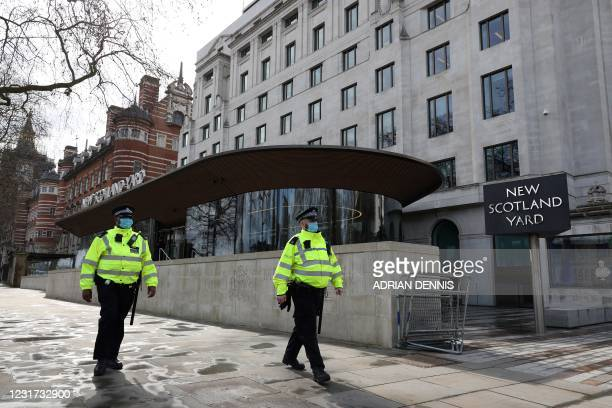 Police officers wearing face coverings due to Covid-19 walk past New Scotland Yard, the headquarters of the Metropolitan Police Service, as...