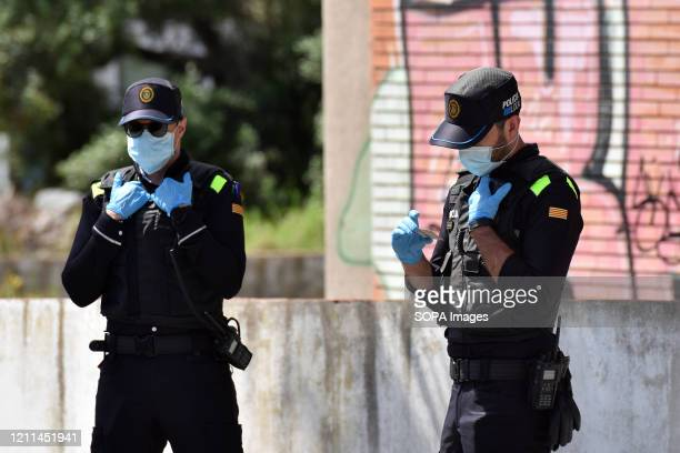 Police officers wearing face masks and gloves at a checkpoint as a preventive measure during the Coronavirus lockdown crisis The Vendrell Local...