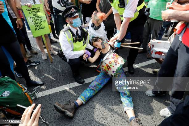 TOPSHOT Police officers wearing face masks and gloves due to the COVID19 pandemic detain an activist from the climate protest group Extinction...