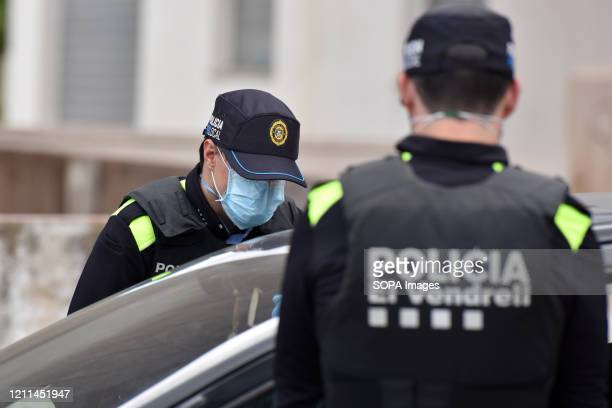 Police officers wearing face masks as a preventive measure stop a driver at a checkpoint to ensure compliance with the rules during the Coronavirus...