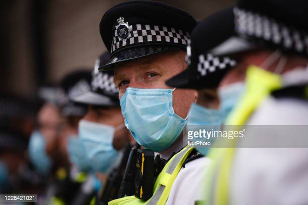 Police officers wearing face masks keep watch nearby activists from climate change activist movement Extinction Rebellion in Parliament Square in...