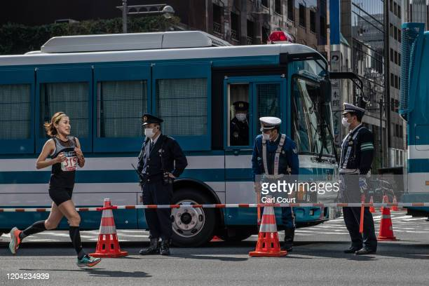 Police officers wearing face masks look on as an elite runner passes by during the Tokyo Marathon on March 1, 2020 in Tokyo, Japan. The 2020 Tokyo...