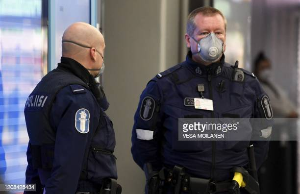 Police officers wearing face masks observe arriving passengers at the Airport in Vantaa Finland on March 27 2020 A large number of Finnish tourists...