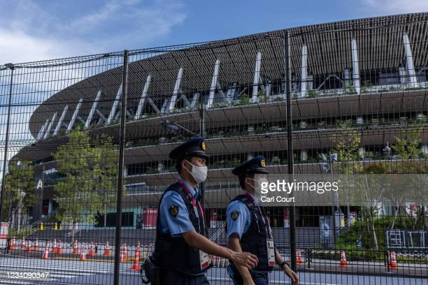 Police officers wearing face masks patrol next to Tokyo Olympic stadium on July 21, 2021 in Tokyo, Japan. With just two days until the Olympics...