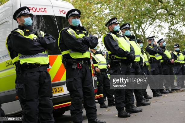 Police officers wearing face masks stand guard as anti-lockdown activists demonstrating against coronavirus restrictions gather in Hyde Park in...
