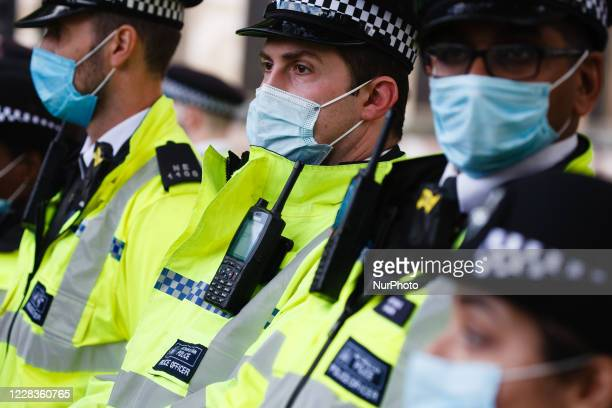 Police officers wearing face masks surround members of climate change activist movement Extinction Rebellion protesting the planned High Speed 2 rail...