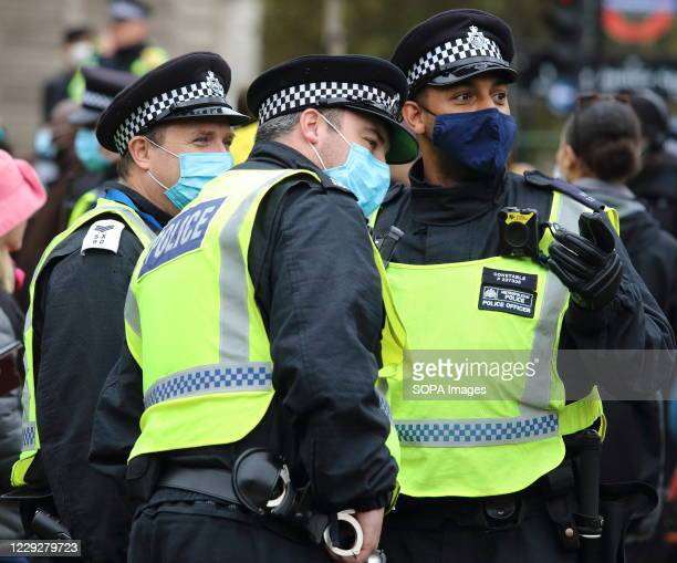 Police officers wearing facemasks are seen having a conversation before the start of the protest. With a number of expected demonstrations taking...