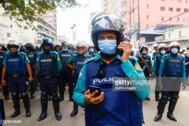 Police Officers wearing facemasks are seen on guard during the protest in Dhaka. Muslims protested calling for the boycott of French products and...