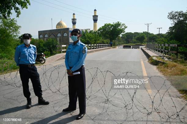 Police officers wearing facemasks stand guard next to a street sealed by the authorities at I-8 residential sector in Islamabad on June 18 as cases...
