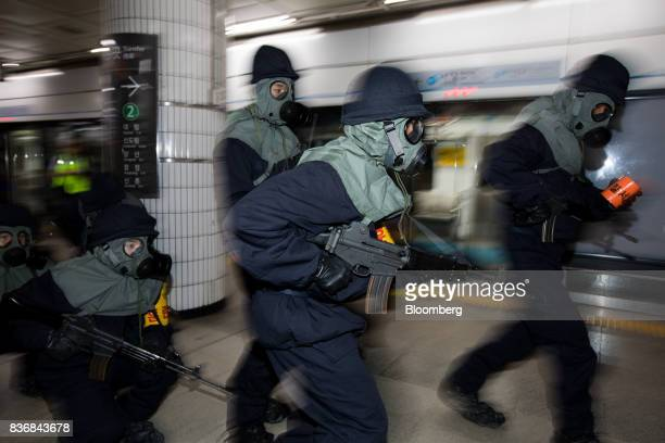 Police officers wearing gas masks participate in an antiterror drill on the sidelines of the Ulchi Freedom Guardian military exercises at a subway...